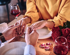 Couple holding hands over Valentine Dinner and wine